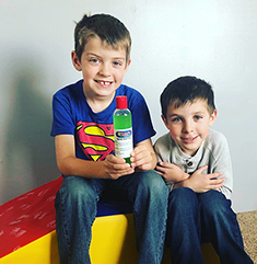 Photo of two boys at child care center with donated hand sanitizer