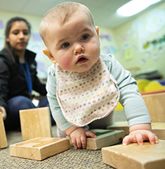 Toddler plays with blocks as caregiver looks on