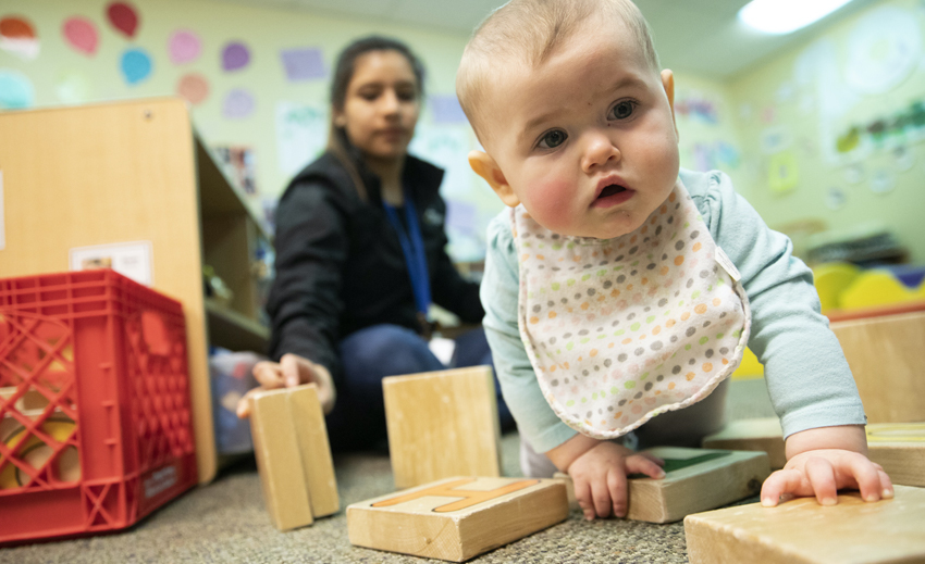 Toddler plays with blocks as child care provider looks on